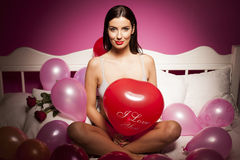 Sexy lingerie woman on the bed with valentines day decorations Stock Photos