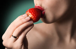 Sexy lips with strawberry. Natural skin. Green background. Hot k Stock Photos