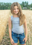 Sexy little girl with long hair posing in wheat field at a summer day. Portrait of a beautiful 8-year-old girl with long hair and green eyes in a golden wheat Stock Photos