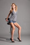 Sexy long legged blonde model sitting on bar stool. Sexy young blonde fashion model girl sitting on bar stool in studio. Model wearing short denim shorts, check Stock Image
