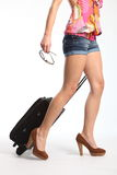 Sexy long legs going on holiday with suitcase. Woman's sexy long legs, wearing high heels and dragging a black suitcase. Woman holding sunglasses in one hand and Royalty Free Stock Photography