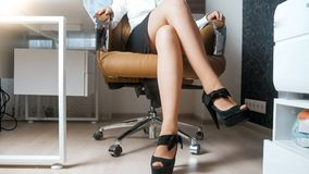 Sexy long legs of young businesswoman sitting in armchair. Sexy legs of young businesswoman sitting in armchair Stock Images