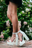 Sexy long woman legs wearing white high heels Stock Image
