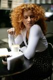 Look of a dreaming happy woman in a cafe. Beautiful young curly redhead woman in dotted black dress dreaming in street cafe on coffee break stock images