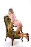 Look of Glamorous girl. There is cute girl looks at you. She hits on her knee on a green chair stock images