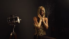 Luxurious portrait of african american female model with glossy golden makeup and glossy headwear posing to. The camera. Bronze bodypaint, black studio stock footage