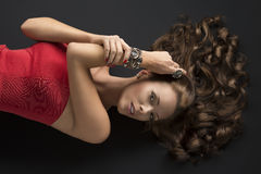 Lying girl with long curly hair and hand near the head. Pretty girl with brown long curly hair lying on the black floor, looks in to the lens, her right hand is royalty free stock images
