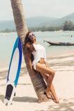 Sexy Mädchen auf tropischem Strand mit Brandungsbrett Lizenzfreie Stockfotos