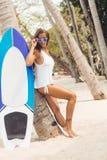 Sexy Mädchen auf tropischem Strand mit Brandungsbrett Stockfotografie