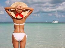 Mädchen auf tropischem Strand. Schöne junge Frau mit Sonnenhut Stockbilder