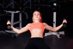 Sexy Mädchen, das Übungen in ihrem Brustmuskel tut Eignung mit Dummköpfen in der Turnhalle nette nette Frau Stockfoto