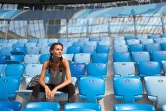 Sexy Mädchen, das am Stadion mit dem Rucksack aufwirft Eignungsmädchen mit Sport erscheinen in den schwarzen Gamaschen, die auf d Lizenzfreie Stockbilder