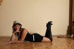 Sexy Mädchen in den Stiefeln und in Hut, die im Innenraum auf Boden aufwerfen Lizenzfreie Stockbilder