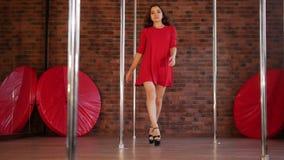 Sexy Mädchen in der roten Kleidertanzenstangentanz Von einem Pfosten unten kommen und geht in Richtung zur Kamera stock video