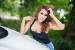 Sexy Mädchen in der schwarzen Weste wirft auf Haubenauto auf Stockfoto