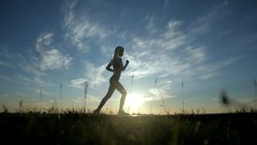 Sexy Mädchen des laufenden Schattenbildes auf Sonnenuntergang
