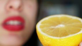 Sexy Mädchen hält in ihrer Hand eine geschnittene Hälfte der gelben saftigen Zitrone stock video