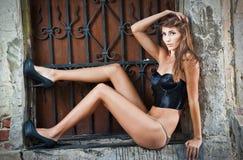 Mädchen im Bikini, der Mode nahe Wand des roten Backsteins auf der Straße aufwirft Lizenzfreies Stockbild