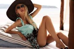 Sexy Mädchen im Hut und in Sonnenbrille, die auf Strand in Phuket sich entspannen Lizenzfreie Stockfotos