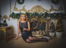 Sexy Mädchen im schwarzen Kleid am Abend, Weihnachtsabend, mit einem Glas Wein Stockbilder