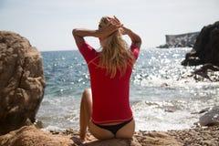 Sexy Mädchen im sportwear und tanga auf dem felsigen Strand Lizenzfreies Stockfoto