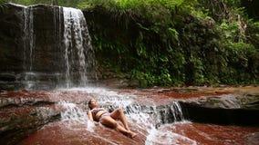 sexy Mädchen mit dem Bikini, der sich im Wasserfallfluß hinlegt stock video