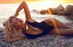 Sexy Mädchen mit dem blonden Haar im Badeanzug, der auf Sonnenuntergang aufwirft Lizenzfreies Stockfoto