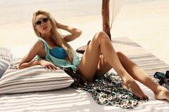 Sexy Mädchen mit dem blonden Haar im Bikini und in Sonnenbrille, die auf Strand sich entspannen Stockbilder