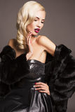 Sexy Mädchen mit dem blonden Haar im Pelzmantel Stockfotos