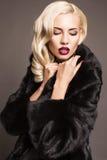 Sexy Mädchen mit dem blonden Haar im Pelzmantel Stockbild