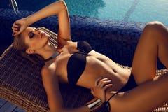 Sexy Mädchen mit dem blonden Haar im schwarzen Bikini, der neben einem Swimmingpool aufwirft Stockbild