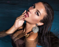 Sexy Mädchen mit dem dunklen Haar, das im Swimmingpool aufwirft lizenzfreie stockbilder