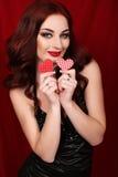 Sexy Mädchen mit dem dunklen Haar trägt das elegante schwarze Kleid und hält rotes Herz Lizenzfreies Stockbild