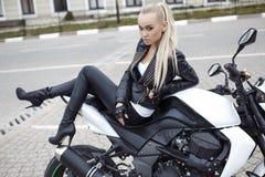 Sexy Mädchen mit dem langen blonden Haar in der Lederjacke, werfend auf Motorrad auf Lizenzfreie Stockfotografie