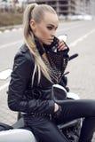 Sexy Mädchen mit dem langen blonden Haar in der Lederjacke, werfend auf Motorrad auf Stockfotos