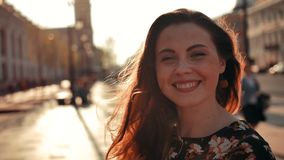 Sexy Mädchen mit dem langen roten Haar, das sich herum dreht und auf der Kamera im Freien lächelt stock video footage