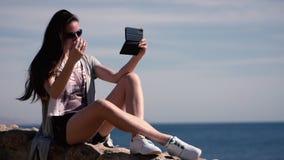 Sexy Mädchen sitzt auf dem Steinzaun und macht selfie auf der Telefonkamera stock video footage