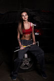 Sexy Mädchenmechaniker, der auf einem Reifen hält einen Schlüssel in seiner Hand sitzt farbloses Lebenkonzept Stockbilder