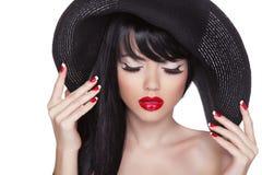 Sexy Mädchenporträt der Schönheitsmode im schwarzen Hut. Rote Lippen und Pol Lizenzfreies Stockfoto