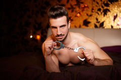 Sexy macho man with handcuffs laying on bed Royalty Free Stock Image