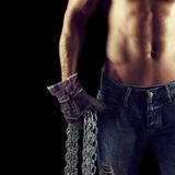 Sexy macho man holding chains in gloves Royalty Free Stock Image