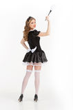 Maid. Rear view of beautiful young maid in white pantyhose. Holding brush and looking over shoulder stock photo