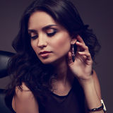 Sexy makeup brunette model looking down with hand near pink earr Royalty Free Stock Image