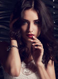 Sexy makeup female model with long curly hair touching dark red Stock Photography