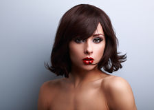 makeup woman with short black hair style and red lipstick. Closeup portrait on blue background Stock Image