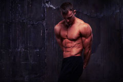 Sexy male fitness model with perfect muscular body against dark Royalty Free Stock Images