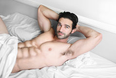 Sexy male model smile in bed Royalty Free Stock Photo