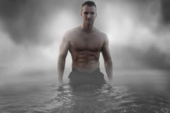 Sexy male standing in the water. Over a cloudy sky Royalty Free Stock Photo