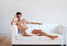 Sexy male underwear model posing on couch Royalty Free Stock Photography