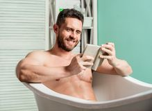 Sexy man in bathroom reading. Macho naked in bathtub. Sex and relaxation concept. man has muscular body. Wash off foam. With water carefully. book lover. macho royalty free stock images